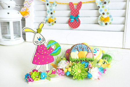 Easter home decor. paper garland with bunnies, wooden bunny figurine with eggs, hand-painted, handmade basket with eggs and gingerbread. Stock Photo