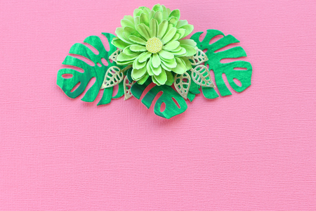 Handmade green paper flower and paper leaves on a pink paper textural background. copy space.