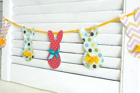 Easter home decor. a garland of bunnies from multicolored paper and tails of yarn hanging on a white wooden wall.