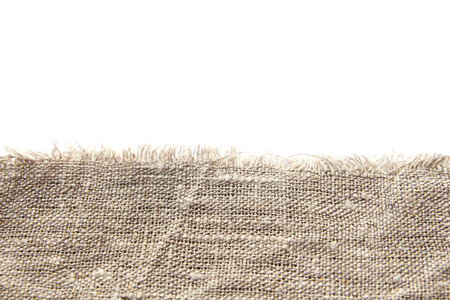 Background and texture of gray coarse linen fabric with close weaving and fringe along the edge on a white isolated background. 免版税图像