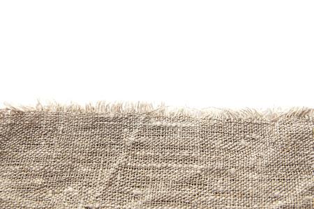 Fondo e struttura del tessuto di lino grezzo grigio con tessitura stretta e frangia lungo il bordo su uno sfondo bianco isolato.