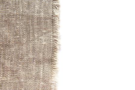 Fond et texture de tissu de lin grossier gris avec tissage étroit et frange le long du bord sur fond blanc isolé. Banque d'images