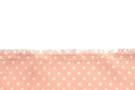 background and texture of dusty cotton fabric with beige polka dots with fringe along the edge on a white isolated background. Archivio Fotografico