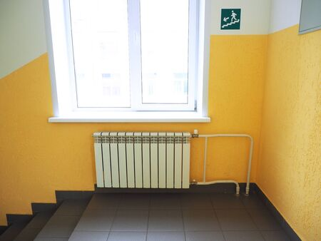Corridor, window with radiator, yellow painted wall and a sign warning about the stairs. Stairs steps.