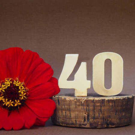 """Golden volumetric number """"40"""" and a red gerbera flower on a brown background. place for text."""