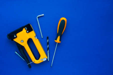 black and yellow construction stapler, screwdriver, drill, furniture key and screw on a blue background. flat layout, top view. Space for text.