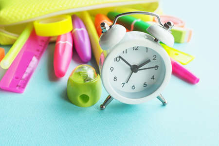 School office supplies: felt-tip pens, markers, sharpener, eraser, pens, tape, rulers of bright neon colors drop out of a yellow pencil case on a blue paper background and a white alarm clock.