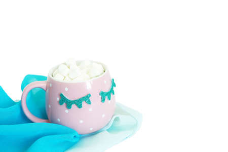 A pink and white polka-dot mug with closed blue eyes with coffee and marshmallows stands on a blue chiffon shawl. Isolate on a white background.