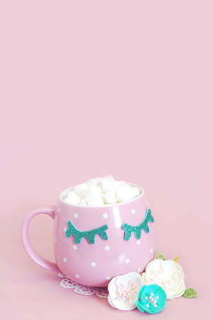 Pink and white polka-dot mug with closed blue eyes with coffee and marshmallows and three artificial flowers on a pink background. Stock fotó