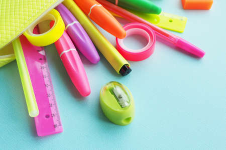 School office supplies: felt-tip pens, markers, sharpener, eraser, pens, tape, rulers of bright neon colors drop out of a yellow pencil case on a blue paper background.