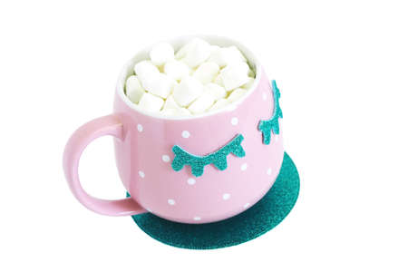 A pink and white polka-dot mug with closed blue eyes with coffee and marshmallows stands on a blue shiny round stand. Isolate on a white background.