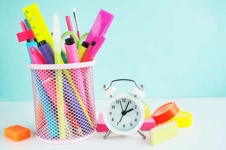 school stationery: felt-tip pens, rulers, pens, pencils and scissors in a mesh basket, multi-colored neon tape, sharpener and white alarm clock on pink stickers.