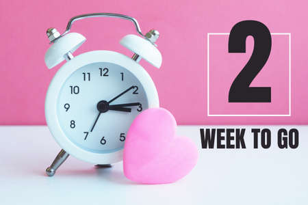 "A small white alarm clock and a pink heart figurine. The inscription ""2 week to go""."