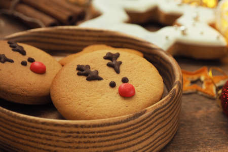 Round cookies with a Christmas deer face with a red nose in a wooden round plate on a wooden table.