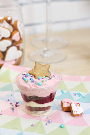 a glass with a puff dessert, decorated with sprinkles and star-shaped gingerbread on a multi-colored towel. A jar of cookies and two glasses in the background.