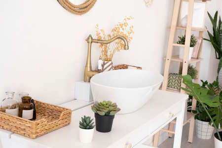 bright bathroom, sink, mixer, mirror, wicker basket and flowers on a white cabinet. Reklamní fotografie