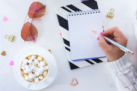 female hands with a beautiful manicure write with a pen in a notebook and a white cup with coffee with marshmallows, sunglasses and heart-shaped sweets. flat layout, top view, lifestyle, 스톡 콘텐츠