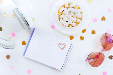 white headphones, a cup with coffee and marshmallows, a notepad and glasses on a white table with confetti hearts. lifestyle, top view, flat layout.