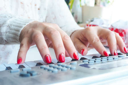 a woman in a white sweater and with red bright nail polish plays the synthesizer. life style.