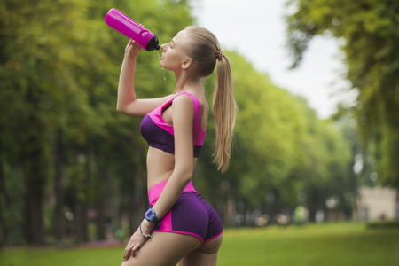 Sexy and sporty girl during the break, drinks water from the bottle Stock Photo