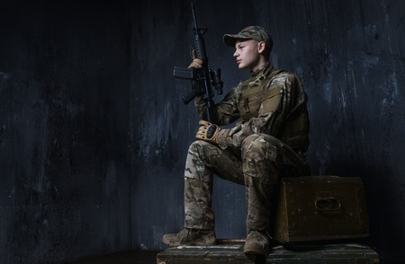 confidently: Young soldier sitting on crates of rifle and confidently looks ahead. Around the world those guys keep us safe Stock Photo