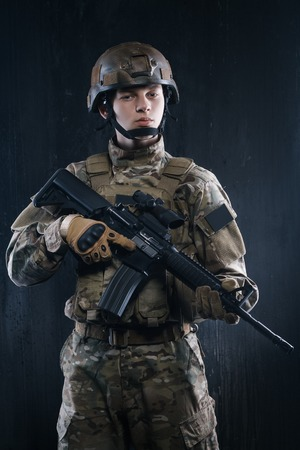 holding gun to head: Proud soldier with his head held high holding a gun and looking confidently forward.soldiers - our pride Stock Photo
