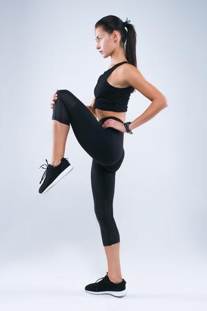 Een aantrekkelijk sportvrouw het uitrekken zich been terwijl status geïsoleerd over grijze achtergrond en weg het kijken Stockfoto