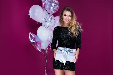 Belle et jolie femme en robe sexy avec des cadeaux et des ballons en studio sur fond rose.