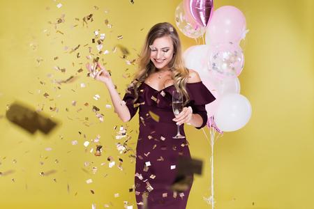 매력적인 여자 축하 생일 및 샴페인과 풍선의 유리와 노란색 배경에 스튜디오에서 춤
