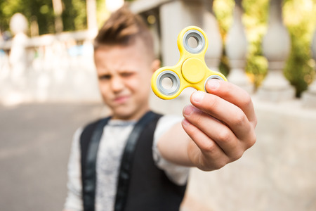 Close up portrait of beautiful boy with yellow spinner and smile. Happy and fun child playing with spinner Stock Photo