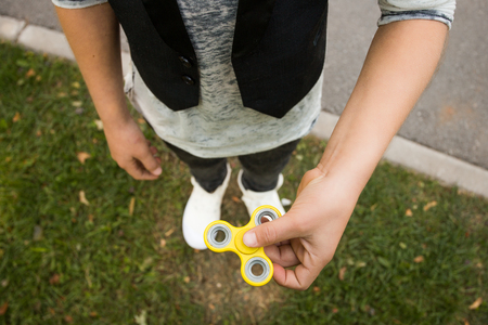 Close up. Boys hands with spinner. Casual beautiful boy in style clothes with spinner Stock Photo
