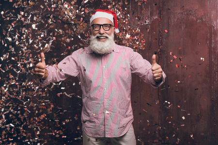 Happy bearded and modern man in Santas hat and in fashionable glasses shows agree good gesture two fingers up and happy smile in gold confetti. Happy New Year 2018 and modern party with fashion Santa