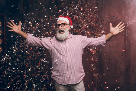 Happy modern Santa wants to hug you Christmas and New year party with Santa in gold confetti. Modern bearded man in Santas hat and fashion glasses have a fun and wants to hug all of the children.