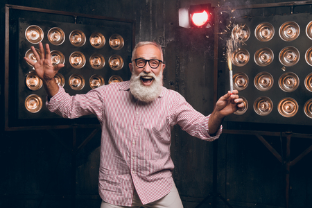 Modern Santa in fashion clothes and in fashionable glasses dancing and have a fun in the club with a sparkle. Happy bearded man on the dark background. Happy Christmas moments. Happy Hew 2018 year