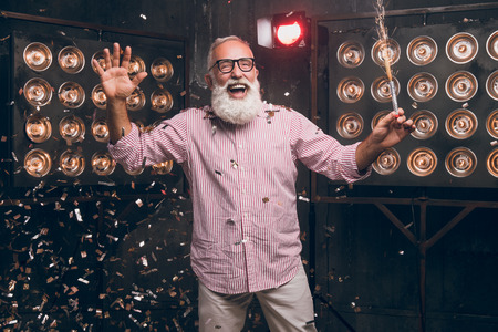 Happy holiday 2018. Christmas time with a modern bearded Santa in fashionable glasses. Santa with a sparkle dancing in gold confetti and have a fun. Waiting for him friends. Christmas feeling.