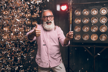Happy Santa Claus shows agree good gesture and have a fun on Christmas party night. 2018 New Year and funny bearded man with sparkle laugh, smile and dancing while waiting midnight to Christmas.