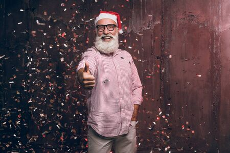 Happy bearded and modern man in Santa's hat and in fashionable glasses shows agree good gesture fingers up and happy smile in gold confetti. Happy New Year 2018 and modern party with fashion Santa Banco de Imagens - 92356600