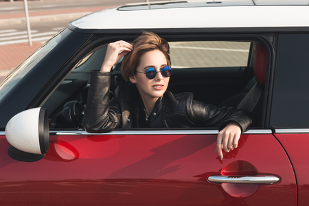 Beautiful girl in leather jacket and sun glasses is looking away while sitting in her car