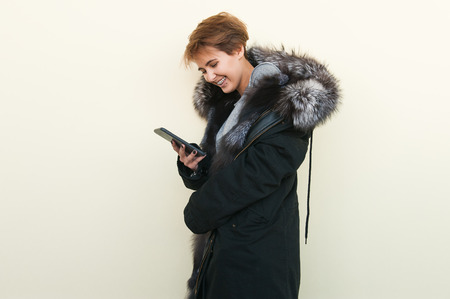 Happy girl in a fur coat uses a phone and she is very happy.