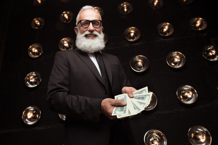 Happy bearded man carry carrying many banknote of dollars and smile, wearing in formal wear and fashion glasses. Looking in the camera. Happy of money prize. Fan of money Banco de Imagens