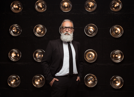 Serious and modern white bearded man posing with a hand in pocket and looking to the camera. Big business rich boss. Wearing in strict suit and fashion glasses