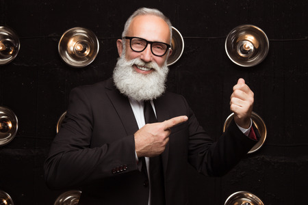 Happy old attractive business man points with a finger at the money. Empty space for money. Bearded man show how he holding money in the suit Banco de Imagens