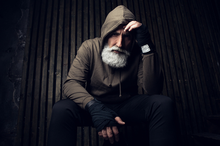 Serious bearded man ready to fight. Sport and fit man in hood thinking about future fight. Workout and box sport. Extreme sport for old man. Close up portrait of man hands over his sports bandages Banque d'images