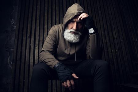 Homme barbu sérieux prêt à se battre. Sport et homme en capuche pensant au combat à venir. Entraînement et boxe sportive. Sport extrême pour le vieil homme. Bouchent le portrait d'un homme les mains sur ses bandages de sport Banque d'images - 89596417