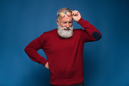 Headache. Old bearded man in red sweeter and in black glasses show headache. Pain emotions isolate on blue background. Stress after hard working office day