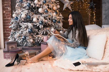 Christmas letter writing on notebook. Many garlands. Christmas , winter holidays and people concept. Letter to Santa Claus. Girl writes her wish Banco de Imagens - 89994130