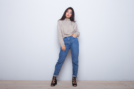 Fashion posing beautiful Asian girl in trendy wearing. Casual wearing in jeans, high heel shoes and sweeter
