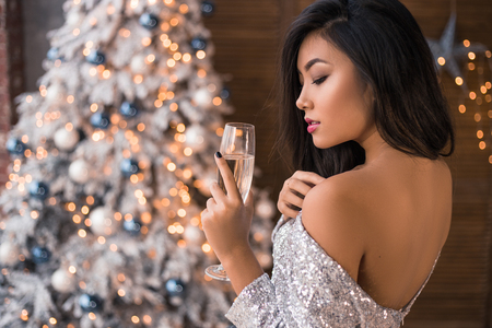 Portrait of lips of attractive young Asian girl with glass of champagne. Sexy dressed girl in sparkle dress drink alcohol while standing in front of Christmas Tree. Happy New Year and 2018 Christmas.