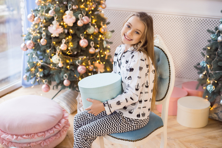 Christmas Concept - Little happy girl sits on a background of Christmas decorations with a gift and smiles. Merry Christmas and Happy Holidays!