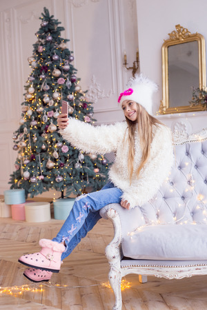 Little happy girl congratulates his friends on Christmas and New Year on video communication in social networks. Stylish and fashionable clothes. Banco de Imagens